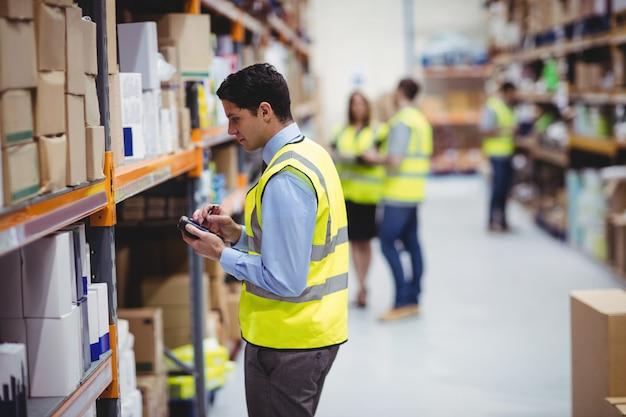 Magasinier à l'aide de scanner à main dans l'entrepôt