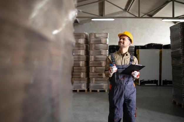 Magasinier comptant des palettes pour la distribution dans le magasin.