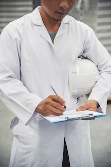 Magasinier vérifiant sa liste sur presse-papiers dans un grand entrepôt