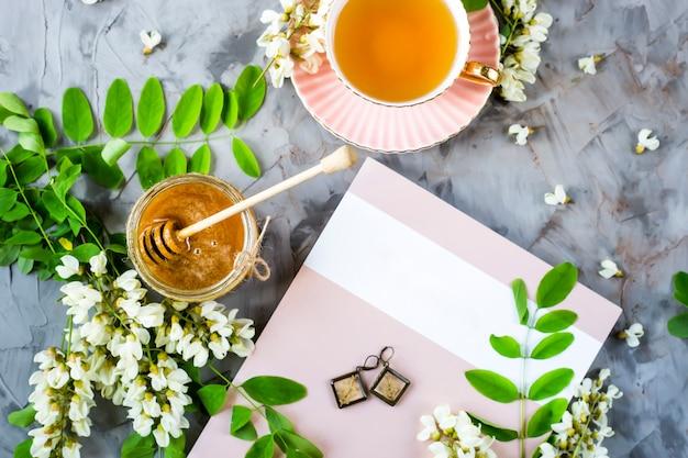 Le magazine à côté d'une tasse de thé et d'un pot de miel