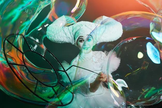 Le magicien artiste de cirque montre des tours avec des bulles de savon.