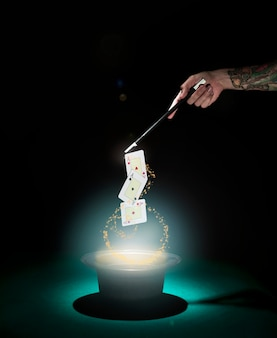 Magicien effectuant un tour de cartes à jouer sur le haut de forme avec des lumières brillantes sur fond noir