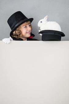 Magicien enfant avec lapin se cachant derrière une affiche vierge.