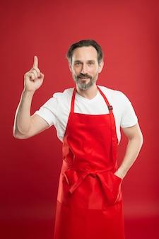 Magie culinaire. cuisiner avec barbe et moustache portant un tablier sur fond rouge. cuisinier mature homme posant un tablier de cuisine. chef cuisinier et cuisinier professionnel. cuisinez à la maison. belle recette. idées et astuces.