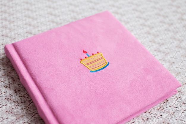 Magnifique album photo en couverture textile rose clair.