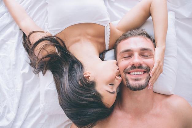 Magnifique et attrayant couple est allongé dans son lit face à face