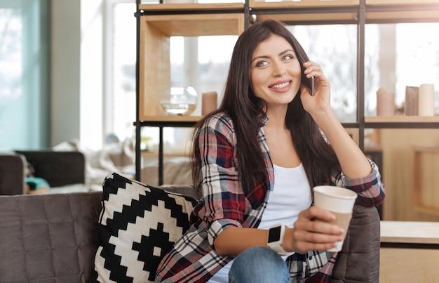 Magnifique bois. heureuse belle femme brune tenant un téléphone portable et le mettre à son oreille tout en ayant une conversation agréable avec quelqu'un