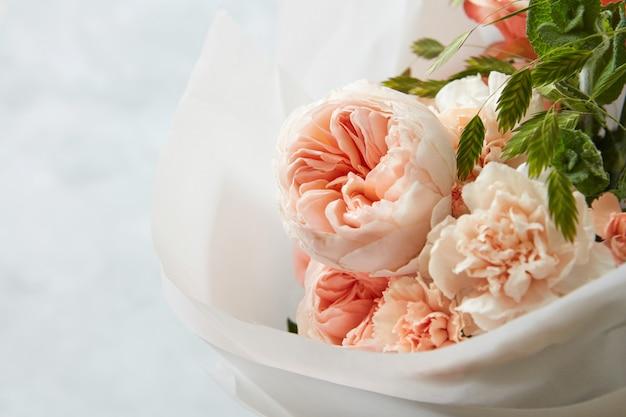 Magnifique bouquet de fleurs de buisson enveloppé dans du papier blanc. mise au point sélective, sur fond blanc