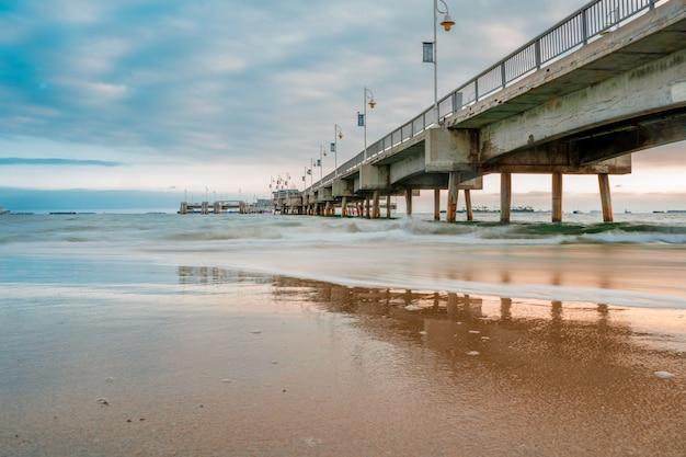 Magnifique coucher de soleil avec une jetée sur la longue plage de los angeles