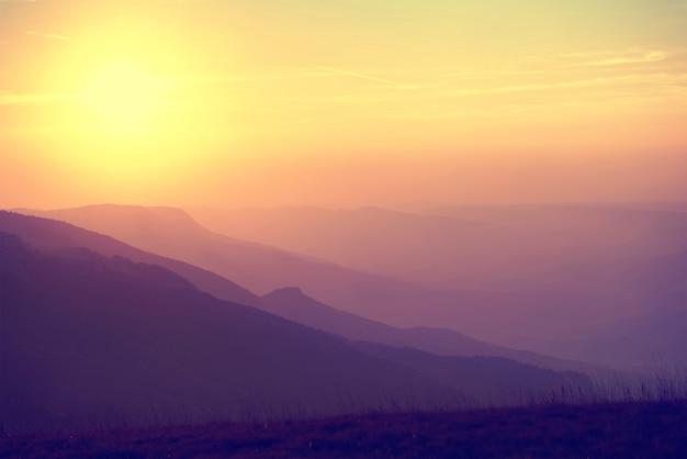Magnifique coucher de soleil sur les montagnes. paysage coloré avec soleil et ciel orange. colorisé comme instagram
