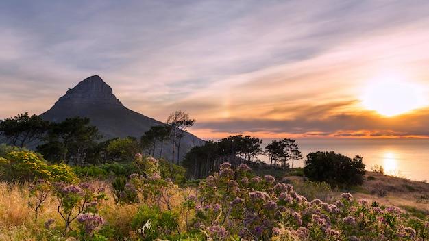 Magnifique coucher de soleil sur l'océan et la vue sur la montagne lion's head depuis signal hill au cap