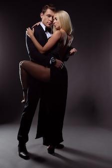 Magnifique couple amoureux en robes de soirée élégantes embrassant passionnément sur fond sombre