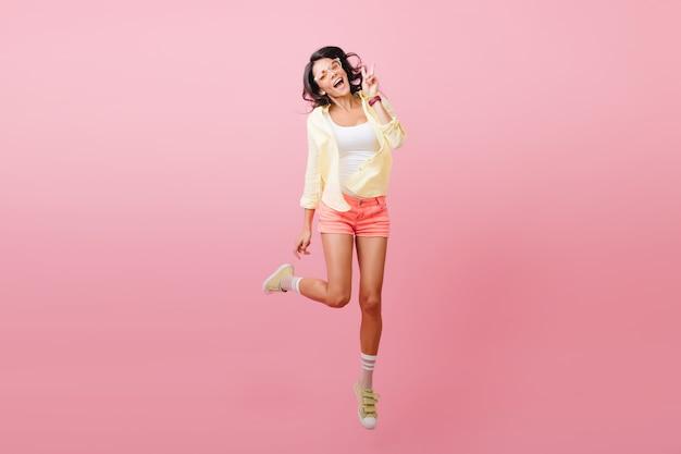 Magnifique femme aux cheveux noirs en tenue tendance debout sur une jambe pour la photo. portrait intérieur de joyeuse jeune femme latine dans des chaussures jaunes élégantes.