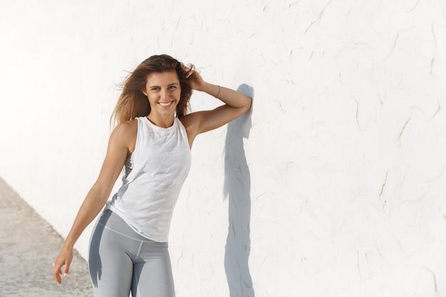 Magnifique femme bronzée caucasienne athlétique fit penché mur de béton à l'extérieur portant des vêtements de sport
