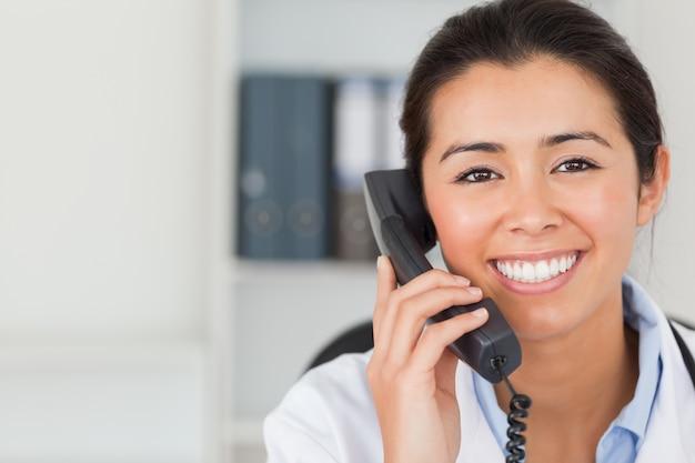 Magnifique femme médecin au téléphone et posant