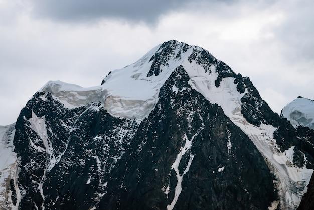 Magnifique gros plan sur le glacier. sommet de montagne sombre enneigé dans un ciel nuageux. crête rocheuse avec neige par temps couvert. magnifique chaîne de montagnes dans la brume. paysage minimaliste atmosphérique, nature majestueuse.