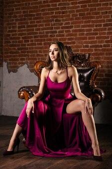 Magnifique jeune femme en robe luxueuse est assise les jambes écartées sur une chaise