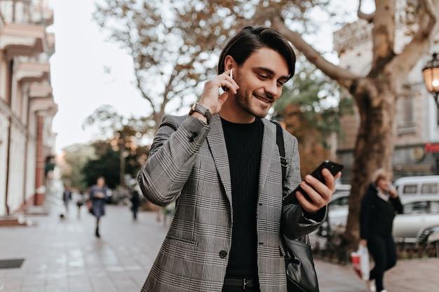Magnifique jeune homme aux cheveux et poils bruns, vêtu d'un blazer de style rétro et d'un casque, tenant un téléphone et une conversation vidéo dans la rue