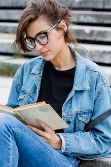 Magnifique livre de lecture féminine assis sur les escaliers