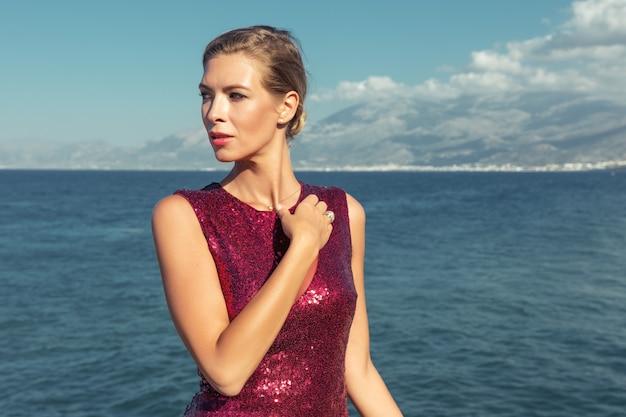 Magnifique mannequin en élégante robe rouge posant sur fond de mer.