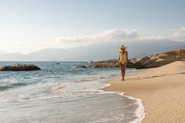 Magnifique mannequin en maillot de bain sur une plage de sable