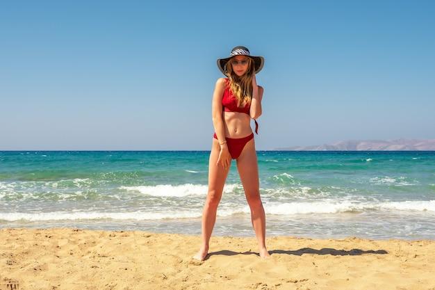 Magnifique mannequin en maillot de bain sur une plage de sable.