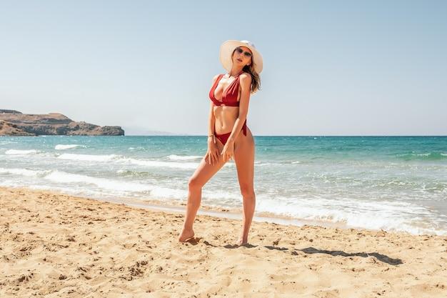 Magnifique mannequin posant sur une plage de sable