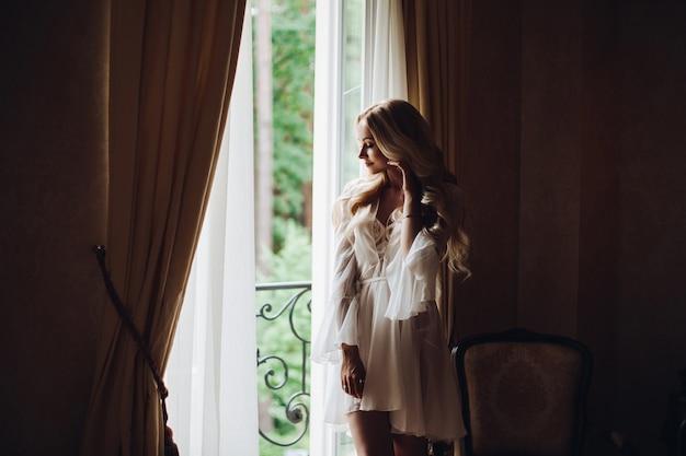 Magnifique mariée debout près du balcon et regardant dans une grande fenêtre