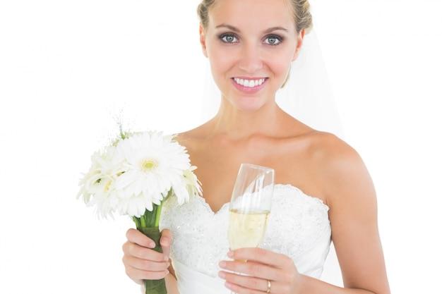 Magnifique mariée tenant un bouquet et un verre de champagne