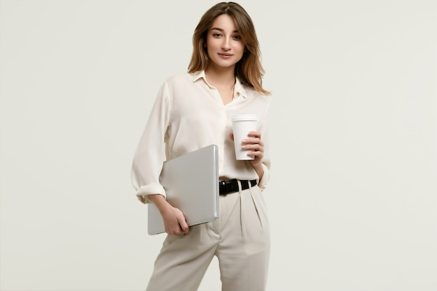 Magnifique modèle brune en vêtements blancs avec ordinateur portable et café