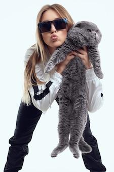 Magnifique modèle fille dans un survêtement posant avec un gros chat de race