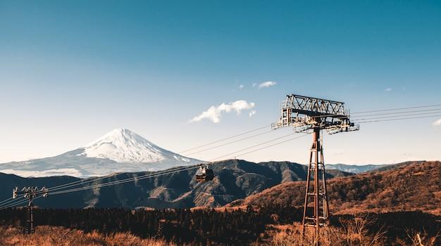 Magnifique montagne fuji recouverte de neige au sommet pendant la saison hivernale au japon avec téléphérique, tons turquoise et orange.