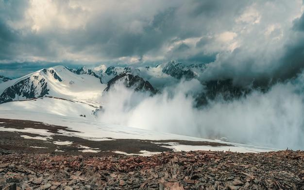 Magnifique paysage dramatique avec de grands sommets enneigés au-dessus de nuages bas. les grands sommets atmosphériques des montagnes enneigées dans un ciel nuageux.