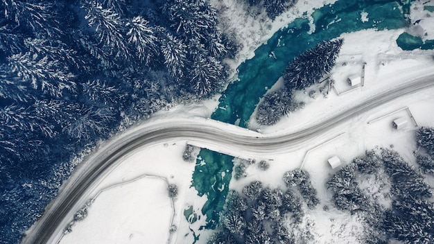 Magnifique paysage de montagne hivernal, route de montagne enneigée avec virages et forêt à l'horizon.