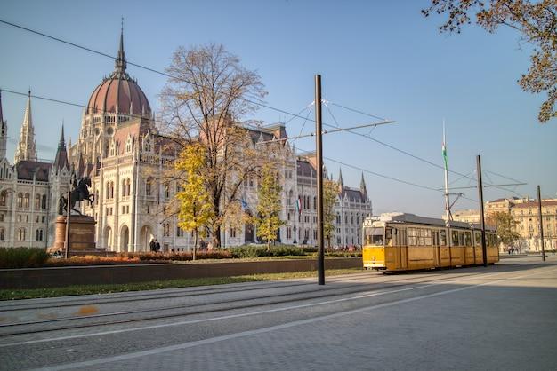 Magnifique paysage urbain de la place avant le bâtiment du palais hongrois avec statue équestre de rakoczi ferenc et tramway jaune en mouvement à budapest, hongrie.
