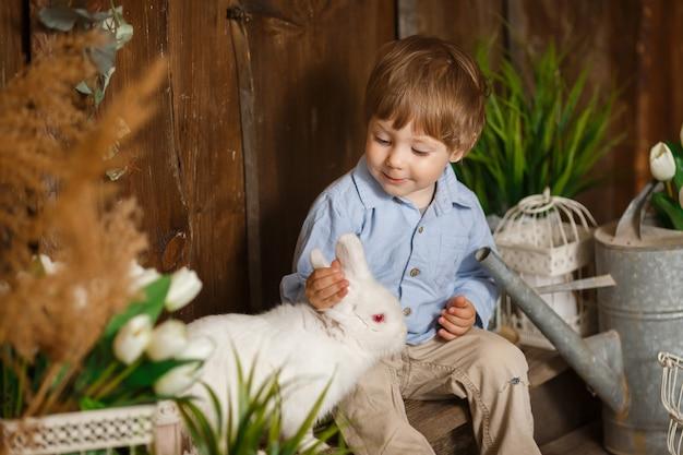 Magnifique petit garçon jouant avec le lapin de pâques dans une herbe verte