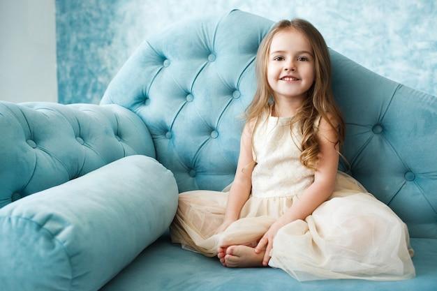 Magnifique petite fille aux cheveux blonds foncés se trouve sur un canapé bleu