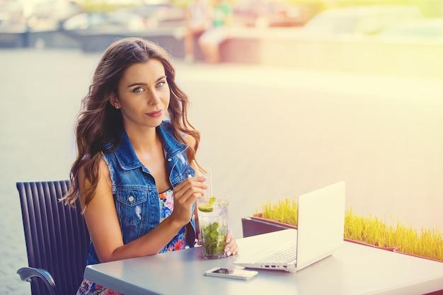 Magnifique pigiste femme joyeuse de bonne humeur, à l'aide d'un ordinateur portable, assis dans les cafés, en sirotant des mojitos