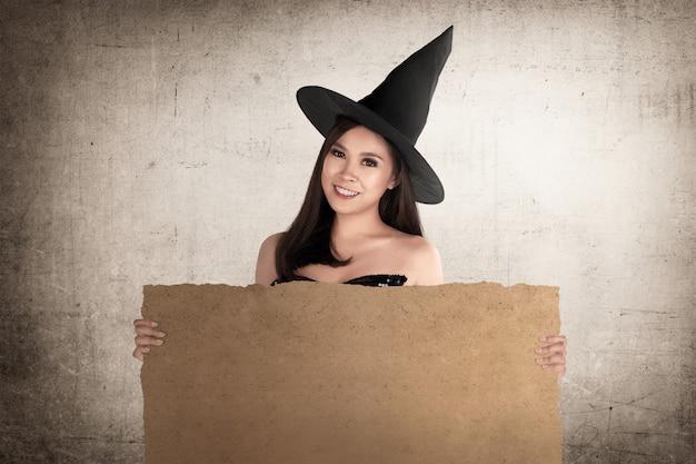 Magnifique sorcière asiatique avec chapeau tenant un papier parchemin vierge