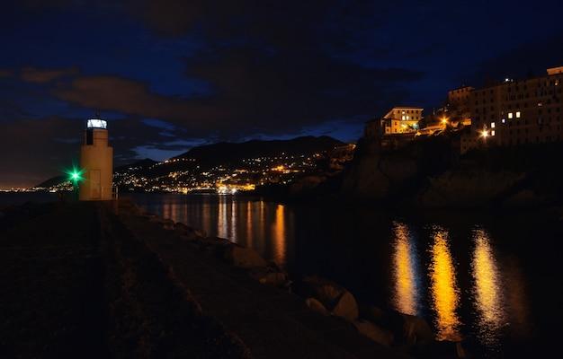 Magnifique vue sur le phare de camogli les lumières et les couleurs se reflètent sur la mer créant un