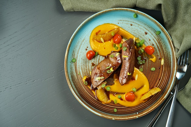 Magret de canard cuit au four en sauce avec purée de carottes et tomates dans une assiette en céramique sur une surface en bois. délicieuse portion de nourriture. vue de dessus, espace copie