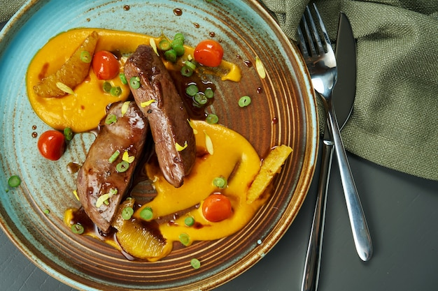 Magret de canard cuit au four en sauce avec purée de carottes et tomates dans une assiette en céramique sur une surface en bois. délicieuse portion de nourriture. vue de dessus, gros plan