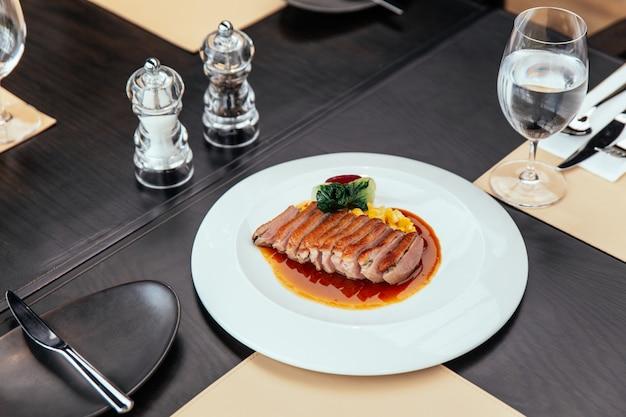 Magret de canard rôti au jus de volaille à la crème de maïs et tamarin, servi avec pain et beurre.