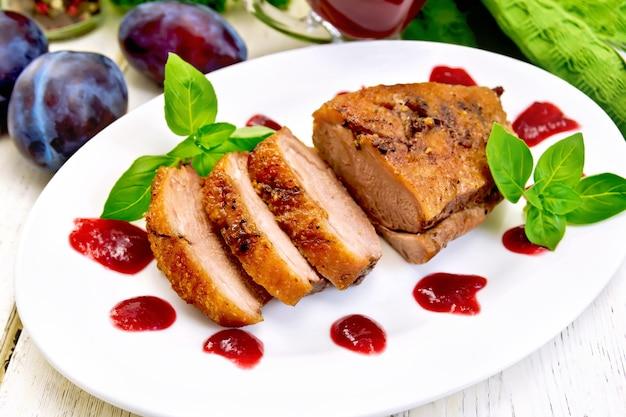 Magret de canard rôti avec sauce aux prunes et basilic dans une assiette ovale blanche, serviette et prunes sur fond de planches de bois clair