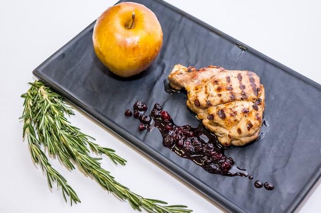Magret de canard à la sauce pomme et baies. canard rôti avec pommes au vin rouge. pommes cuites et viande grillée sur la plaque noire.