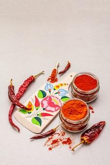 Magyar (hongrois) poudre de paprika rouge sucré et chaud. motif traditionnel sur une planche à découper, différentes variétés de poivre sec.