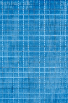 Maille métallique à cellules carrées sur fond bleu