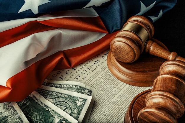 Maillet de juge en bois avec des billets en dollars sur le drapeau américain