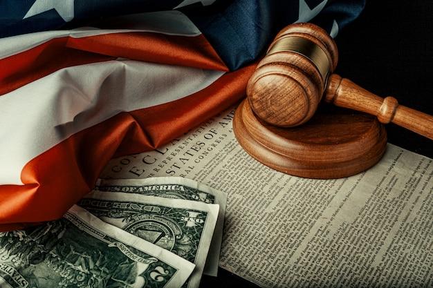 Maillet de juge en bois avec des notes de dollars sur le drapeau américain avec déclaration d'indépendance
