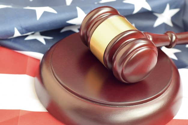 Maillet de justice sur le drapeau des états-unis dans une salle d'audience lors d'un procès judiciaire. concept de droit et fond vide. marteau de juge